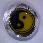 Yellow and black yin Yang glass millie image